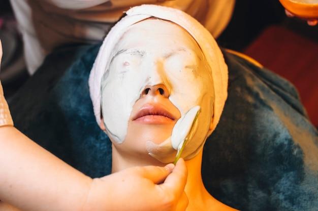 Widok z góry na uroczą kobietę wykonującą alpejską maskę nawilżającą w ośrodku wellness.