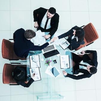 Widok z góry na uścisk dłoni partnerów biznesowych po dyskusji nad nowym traktatem fiskalnym. zdjęcie to puste miejsce na tekst