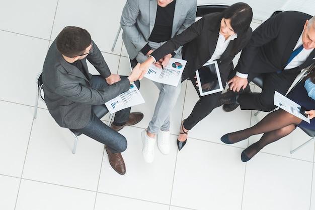 Widok z góry na uścisk dłoni współpracowników podczas spotkania roboczego