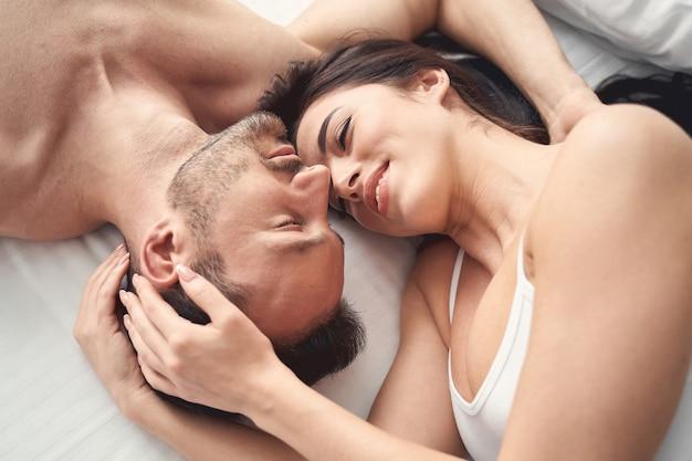 Widok z góry na uśmiechniętą, senną, spokojną ciemnowłosą kobietę leżącą w łóżku z mężem
