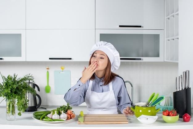 Widok z góry na uśmiechniętą szefową kuchni i świeże warzywa ze sprzętem do gotowania i wykonywanie gestu pocałunku do kogoś w białej kuchni