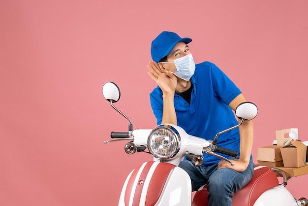 Widok z góry na uśmiechniętego kuriera w masce medycznej w kapeluszu siedzącym na skuterze, słuchającym ostatnich plotek na pastelowej brzoskwini