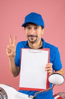 Widok z góry na uśmiechniętego męskiego dostawcę w kapeluszu siedzącym na skuterze pokazującym dokument wykonujący gest zwycięstwa