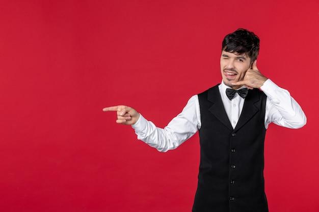 """Widok z góry na uśmiechniętego, szczęśliwego kelnera w mundurze z muszką i wykonującego gest """"zadzwoń do mnie"""", wskazujący coś na prawą stronę"""