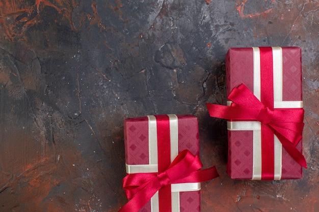Widok z góry na wakacje w czerwonym opakowaniu z czerwoną kokardą na ciemnym kolorze powierzchni prezent na perfumy!