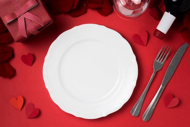 Widok z góry na walentynkowy stół z talerzem i prezentem