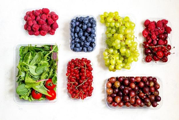 Widok z góry na warzywa, owoce, jagody w plastikowych pudełkach na białym tle