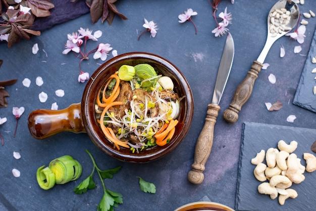 Widok z góry na wegański posiłek z grzybami, cebulą, marchewką i porem