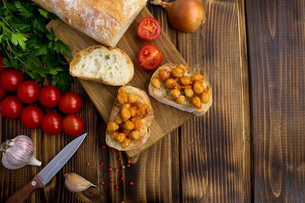 Widok z góry na wegetariańskie kanapki z ciecierzycą w sosie pomidorowym na drewnianej desce do krojenia
