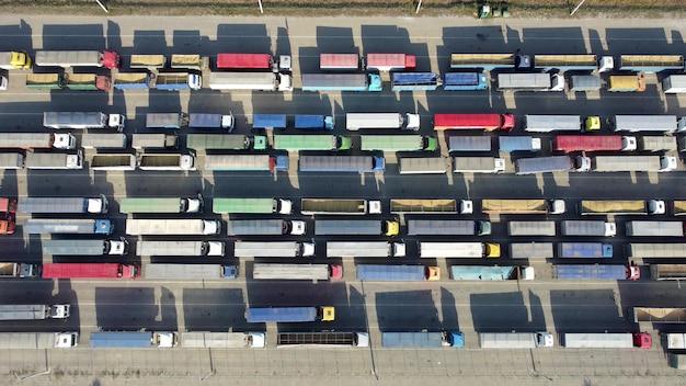 Widok z góry na wiele ciężarówek z przyczepami czekającymi na rozładunek w terminalu portowym.