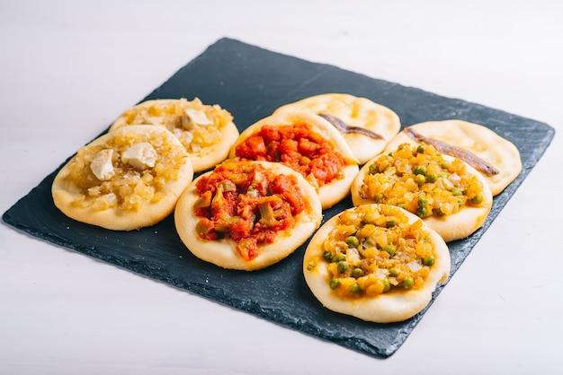 Widok z góry na wiele świeżo upieczonych mini pizz. tradycyjne hiszpańskie ciasto z warzywami.