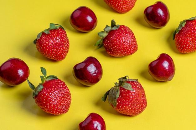 Widok z góry na wiśnie i truskawki w kształcie kwadratu. zdrowa żywność, kuchnia wegetariańska, świeże owoce, płaskie lay