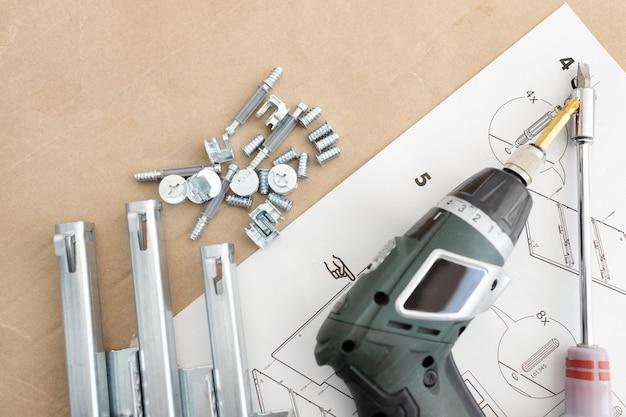 Widok z góry na wkrętarkę akumulatorową, prowadnice szuflad, śruby i akcesoria. koncepcja montażu mebli. skopiuj miejsce