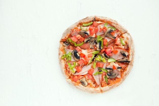 Widok z góry na włoską pizzę na białym stole z pieczarkami, oliwkami pomidorowymi i prosciutto z serem