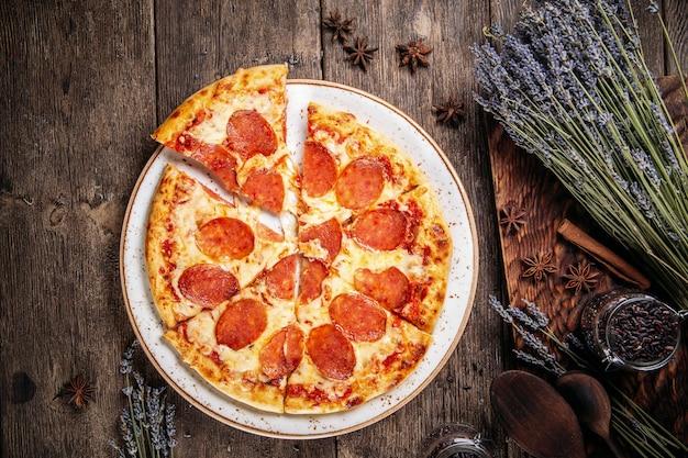 Widok z góry na włoską świeżą pieczoną pizzę pepperoni na drewnianym stole