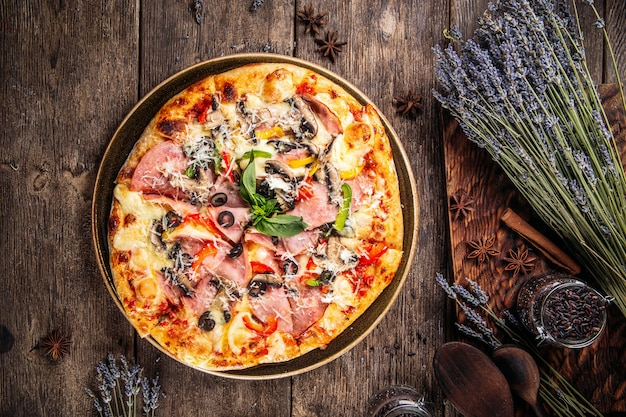 Widok z góry na włoską świeżo upieczoną puszystą pizzę z oliwkami, szynką i pomidorami