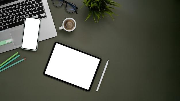 Widok z góry na współczesny obszar roboczy z izolowanym białym wyświetlaczem tabletu, telefonu komórkowego, laptopa i sprzętu na szarym stole.