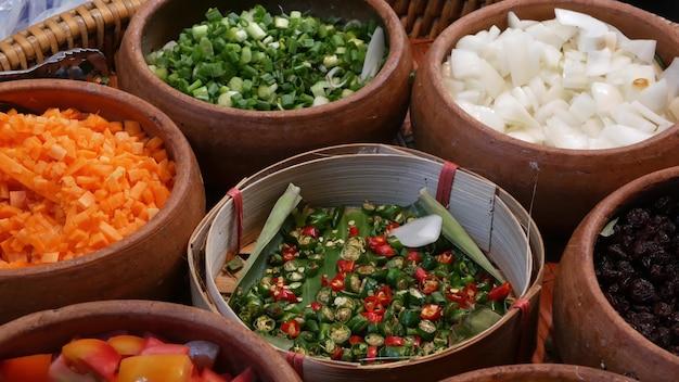 Widok z góry na wybór różnych półmisków z pysznym azjatyckim jedzeniem i przyprawami na straganie ulicznym w bangkoku w tajlandii.