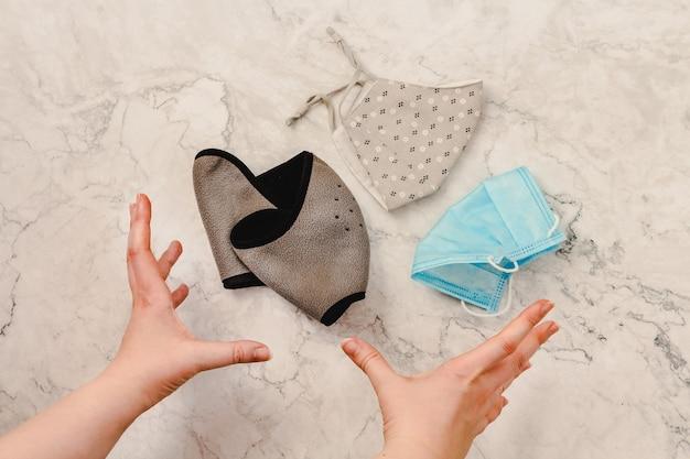 Widok z góry na wyciąganie rąk po maskę higieniczną, aby zapobiec wirusowi koronawirus. maska oddechowa z pięknej tkaniny. kolor beżowy naturalny, szary i niebieski. koncepcja pandemii covid-19.