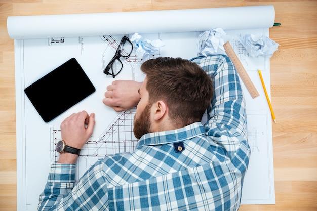 Widok z góry na wyczerpanego brodatego młodego architekta śpiącego w miejscu pracy