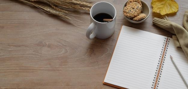 Widok z góry na wygodne jesienne miejsce do pracy z otwartym notatnikiem i filiżanką kawy z artykułami biurowymi