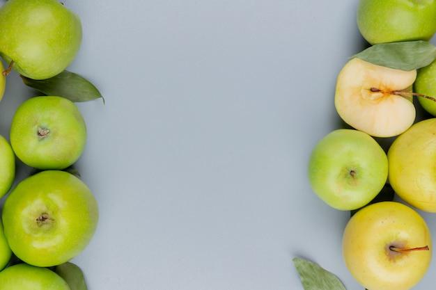 Widok z góry na wzór ciętych i całych jabłek po bokach na szarym tle z miejsca na kopię