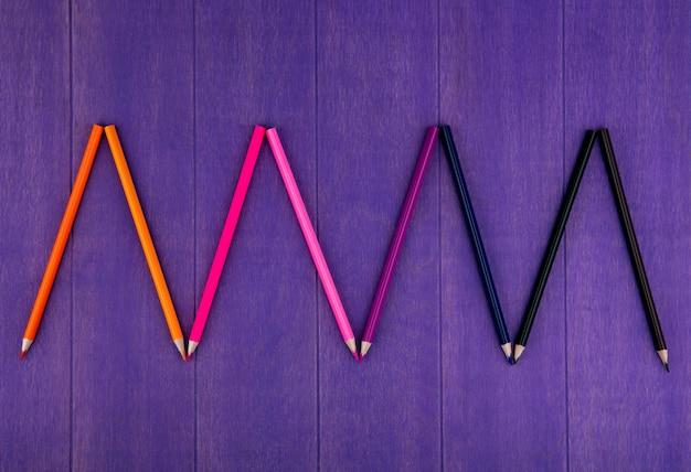 Widok z góry na wzór kolorowych kredek na fioletowym tle