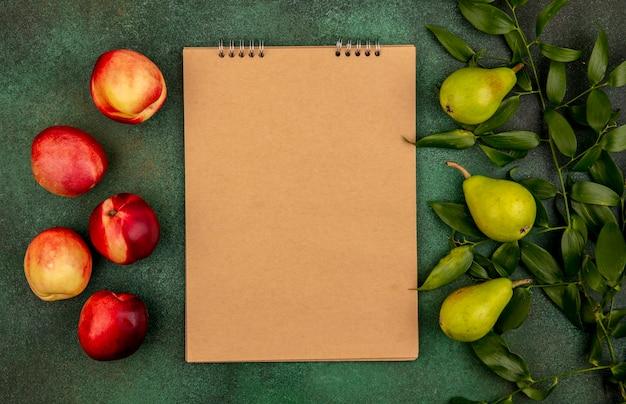 Widok z góry na wzór owoców jak brzoskwinie i gruszki z liśćmi i notesem na zielonym tle z miejsca na kopię