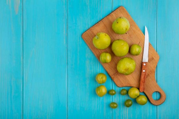 Widok z góry na wzór owoców jako działki i śliwki z nożem na desce do krojenia i na niebieskim tle z miejsca na kopię