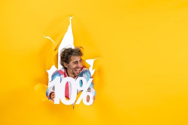 Widok z góry na zabawnego i emocjonalnego młodego mężczyznę pokazującego dziesięć procent w rozdartej dziurze w żółtym papierze
