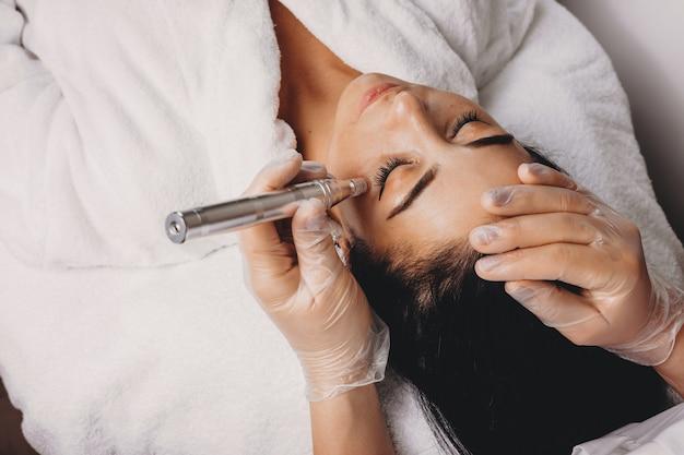 Widok z góry na zabieg pielęgnacyjny skóry ca wykonany nowoczesnym aparatem w salonie spa