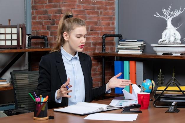 Widok z góry na zadziwioną młodą kobietę siedzącą przy stole i skoncentrowaną na czymś w biurze