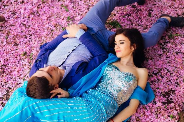 Widok z góry na zakochaną parę leżącą na ziemi wśród płatków kwiatów