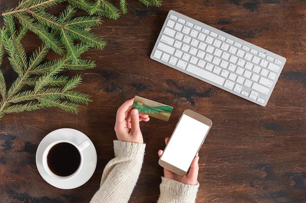 Widok z góry na zakupy online, kartę kredytową i smartfon z pustego ekranu na ręce kobiety