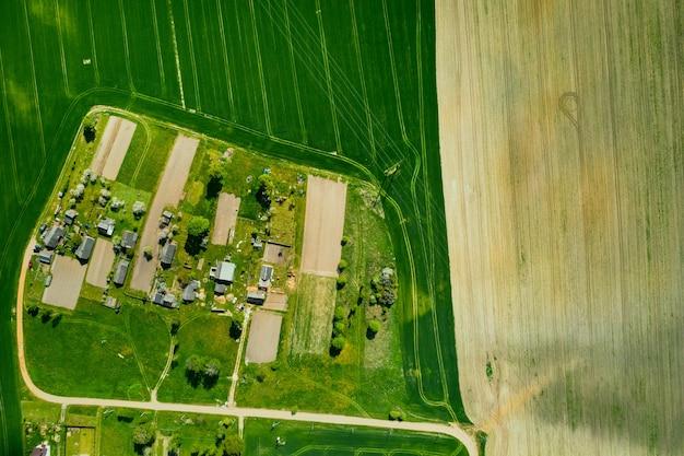 Widok z góry na zasiane zielone pole i małą wioskę na białorusi. pola uprawne we wsi wiosną siew w małej wiosce.