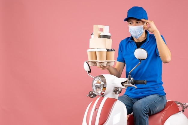 Widok z góry na zaskoczonego dostawcę w masce w kapeluszu, siedzącego na skuterze, dostarczającego zamówienia na brzoskwinię