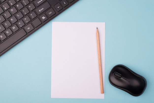 Widok z góry na zdjęcie arkusza papieru z klawiaturą i myszą bezprzewodową