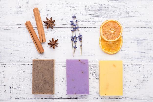 Widok z góry na zdjęcie naturalnego ręcznie robionego mydła z anyżem cynamonowo-lawendowym pomarańczowym na białym tle drewnianych
