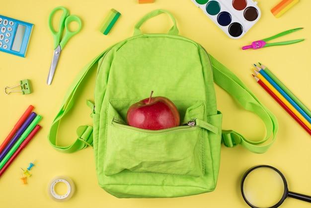 Widok z góry na zdjęcie z zielonego jabłka plecaka kolorowej papeterii na żółtym tle
