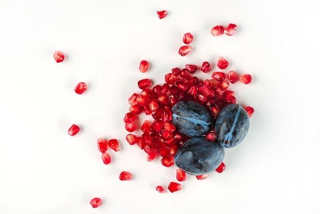 Widok z góry na zdrową koncepcję z soczystymi świeżymi owocami, śliwkami i nasionami granatu