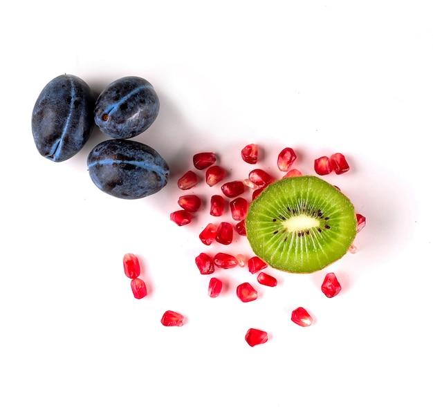 Widok z góry na zdrową koncepcję z soczystymi świeżymi owocami, śliwkami, kiwi i nasionami granatu