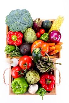 Widok z góry na zdrowe świeże warzywa w drewnianych pudełkach na białym tle, zdrowa żywność