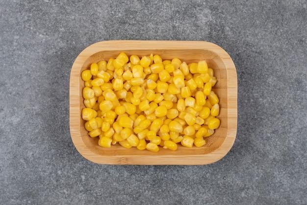 Widok z góry na zdrowe warzywa. nasiona kukurydzy w puszkach w drewnianej misce