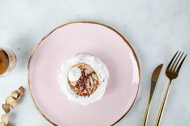 Widok z góry na zdrowe wegańskie desery anna pavlova na biały marmurowy stół z zastawą kawową i spożywczą. skopiuj miejsce na projekt. świeży wegański surowy deser. zdrowe jedzenie. słodkie ciasto bezowe