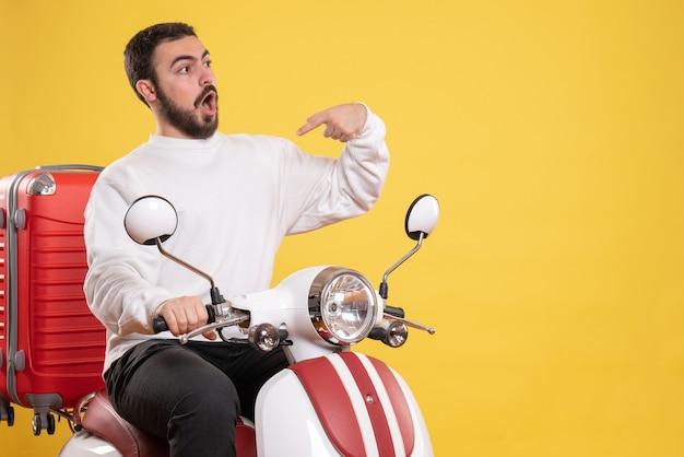 Widok z góry na zdziwionego młodego faceta siedzącego na motocyklu z walizką i wskazującego się na żółto