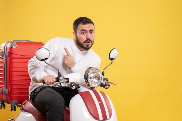 Widok z góry na zdziwionego młodego faceta siedzącego na motocyklu z walizką na nim i wskazującego na żółto