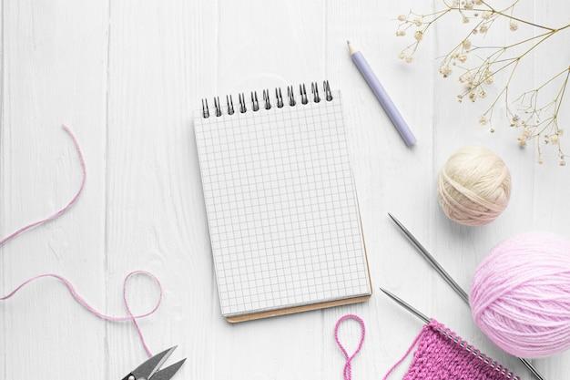 Widok z góry na zestaw dziewiarski z notatnikiem