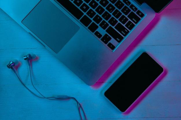 Widok z góry na zestaw gadżetów w fioletowym świetle neonowym i niebieskim
