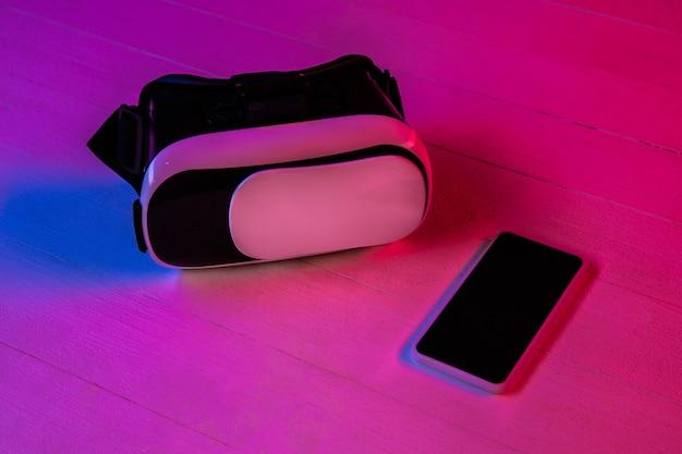Widok z góry na zestaw gadżetów w fioletowym świetle neonowym i różowym tle. smartfon i zestaw słuchawkowy vr. copyspace dla twojej reklamy. tech, nowoczesne, gadżety. wirtualna rzeczywistość.