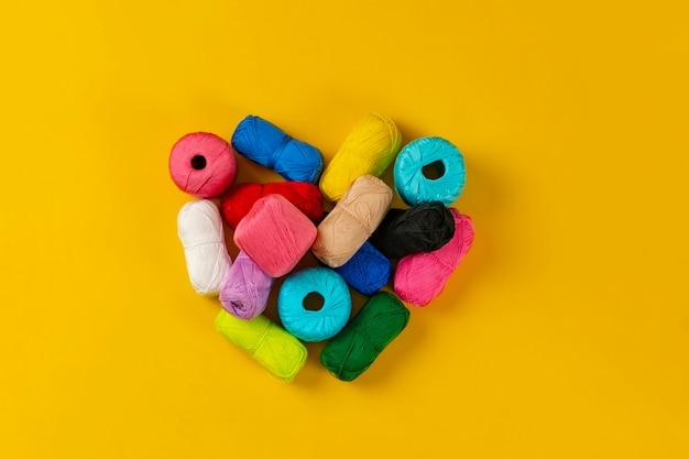 Widok z góry na zestaw kolorowych rolek przędzy w kształcie serca na białym tle